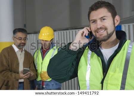 Man in protective wear using cellphone with colleague in background at factory - stock photo