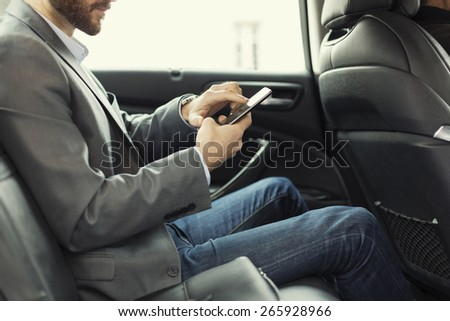 Man in rear of the car. Typing text message on cell phone - stock photo