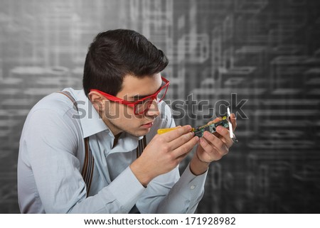 Man in red-framed glasses fixing an electronic card - stock photo