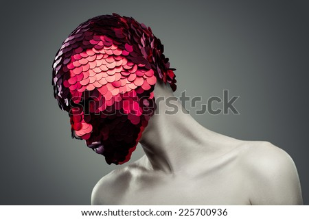 Man in red shiny mask on gray background - stock photo