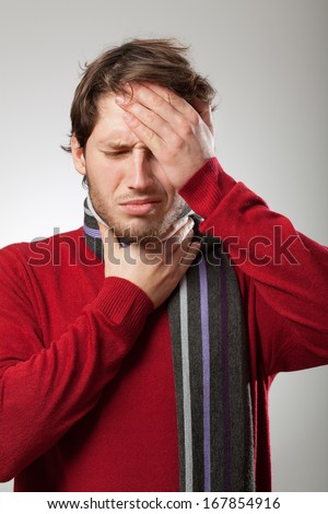 Man in red sweater and scarf has a strong flu symptoms  - stock photo