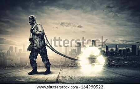 Man in respirator against catastrophe background. Recycle concept - stock photo