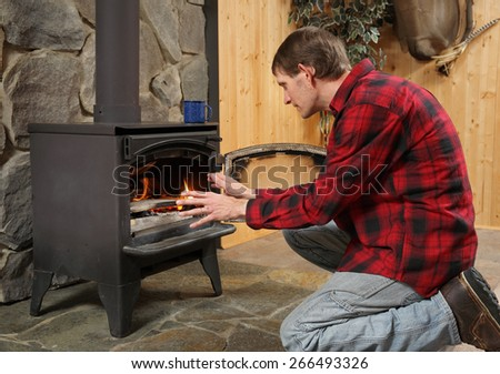 man in rustic setting warming hands by wood stove - stock photo