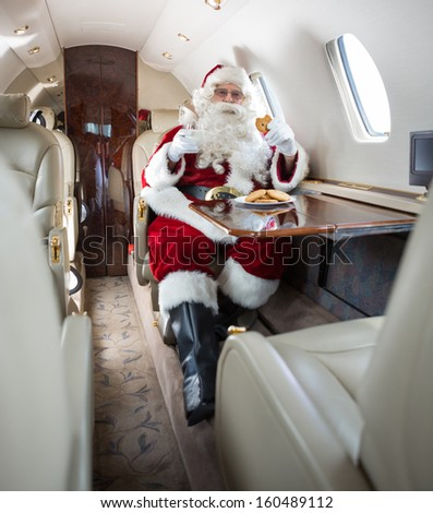 Man in Santa costume having cookies and milk in private jet - stock photo