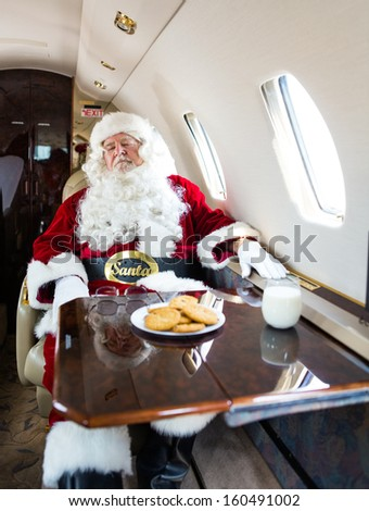 Man in santa costume relaxing on private jet - stock photo