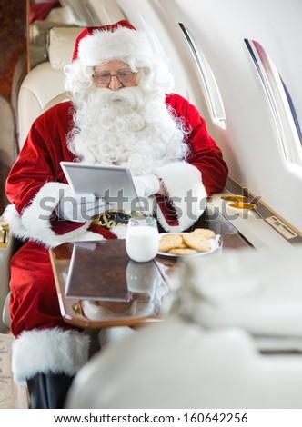 Man in Santa costume using digital tablet in private jet - stock photo