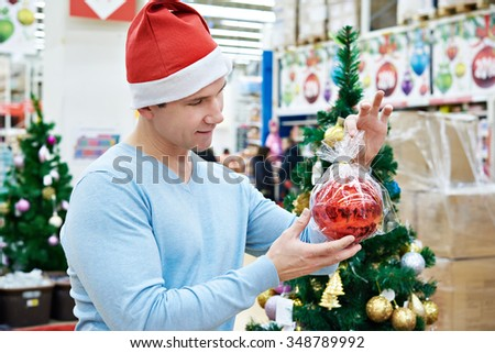 Man in Santa hat holding a red ball Christmas tree at supermarket - stock photo