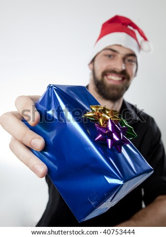 Man in Santa Hat holding out present to camera