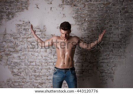 Man in search of answers to questions. Man with a naked torso. A handsome Man with Perfect Body image studio. Pointing hand gesture