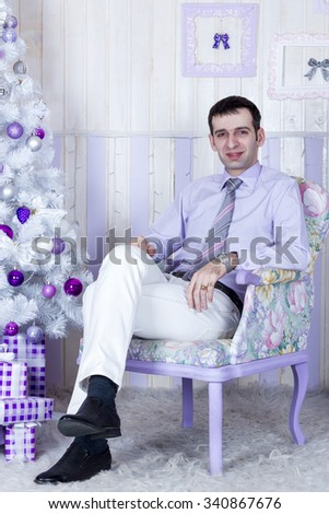 Man in shirt and tie sitting in a chair next to a white Christmas tree with gifts - stock photo