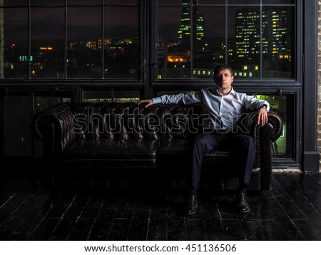 Man in shirt sitting in a leather chair on a background of a brick wall and a window through which one can see the city nightlife