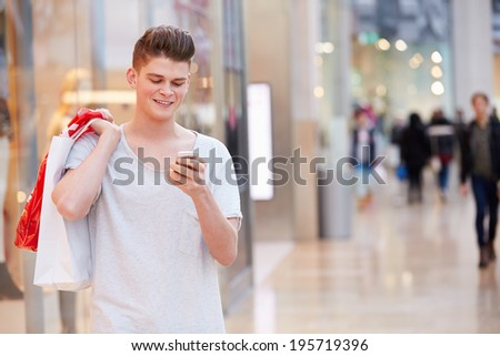 Man In Shopping Mall Using Mobile Phone - stock photo