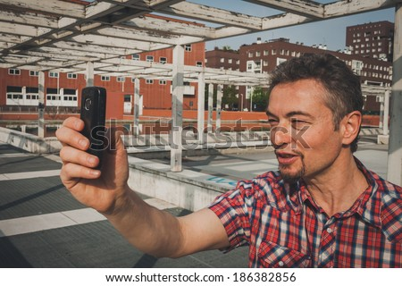 Man in short sleeve shirt taking a selfie in the street