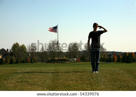 man in silhouette outside with American flag