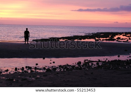 Man in silhouette standing on beach in colorful pink sunset - stock photo