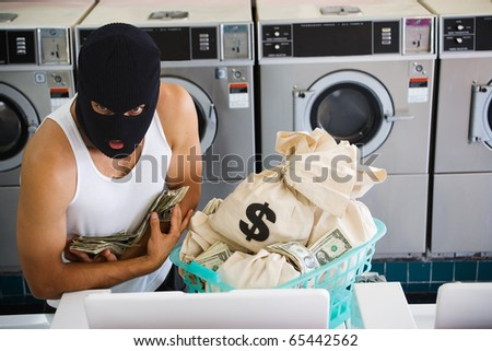 Man in ski mask with bags of money at laundromat - stock photo