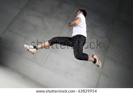 Man in sportswear running up a stairway - stock photo