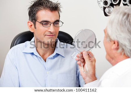 Man in stylish reading glasses while looking at mirror with optometrist in the clinic