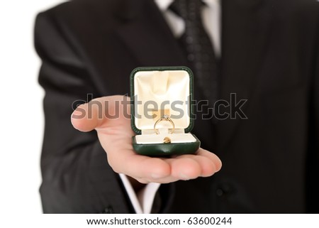 Man in suit and tie holding engagement ring - stock photo