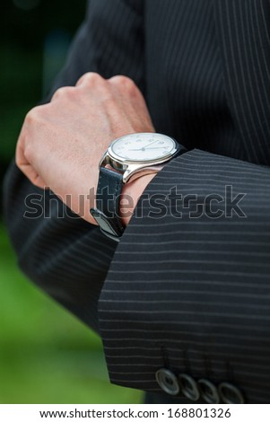 Man in suit checking the time on designer watch