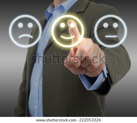 Man in suit choosing a smiley face on a survey panel - stock photo