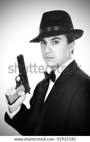 Man in suit draws vintage handgun, white collar outfit. - stock photo