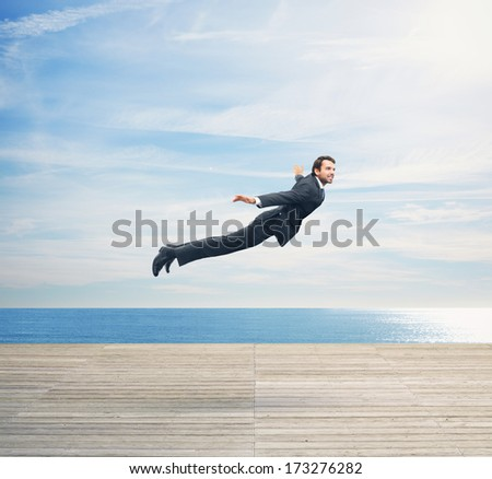 Man in suit flying over boardwalk - stock photo