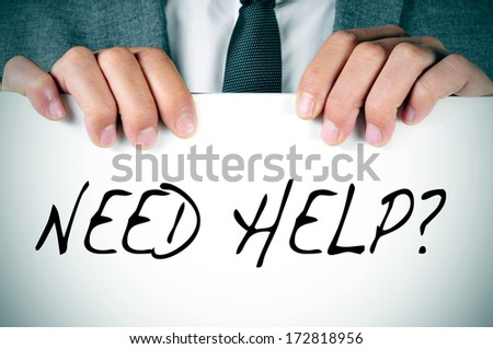 man in suit holding a signboard with the text need help? written in it - stock photo