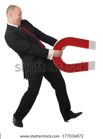 man in suit holding a strong magnet pulling against isolated white space - stock photo