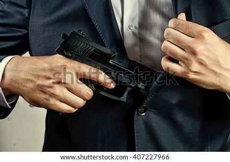man in suit holding gun - stock photo