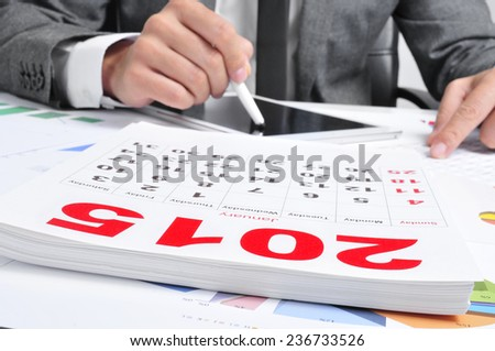 man in suit in his office using a tablet with a 2015 calendar in the foreground - stock photo