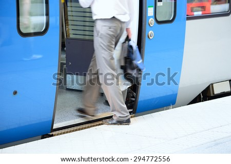 Man in suit in hurry enters train - stock photo
