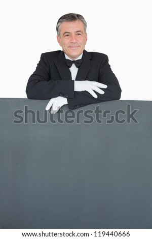 Man in suit leaning on grey board with crossed arms