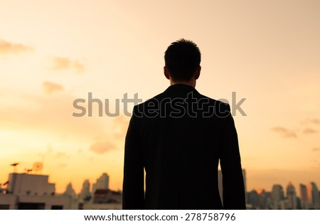 Man in suit looking at the city in the distance.  - stock photo