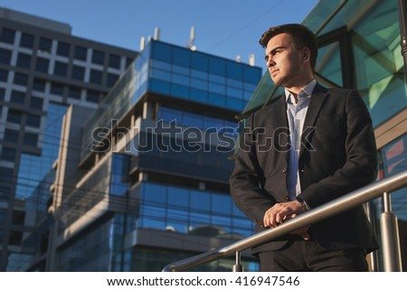 Man in suit on the background of the building with a glass facade