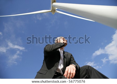 Man in suit phoning near a wind turbine