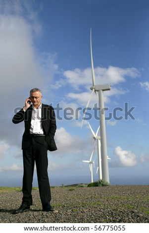 Man in suit phoning near wind turbines