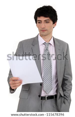 Man in suit reading document - stock photo