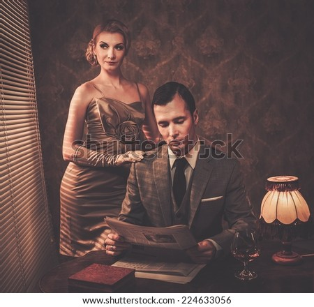 Man in suit reading newspaper with woman behind him - stock photo