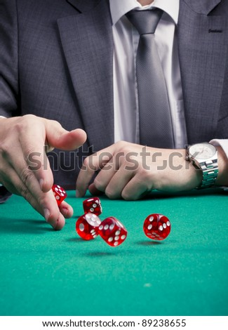 Man in suit rolling dices