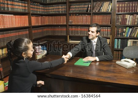 Man in suit shakes hands with woman seated across desk. She is wearing black and they are smiling at each other. Horizontally framed photo. - stock photo