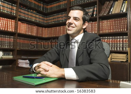 Man in suit sits behind desk. He is smiling with hands crossed on desk. Horizontally framed photo. - stock photo