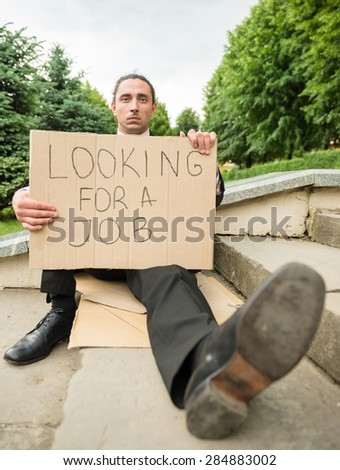 Man in suit sitting at stairs with sign. Unemployed man looking for job. - stock photo