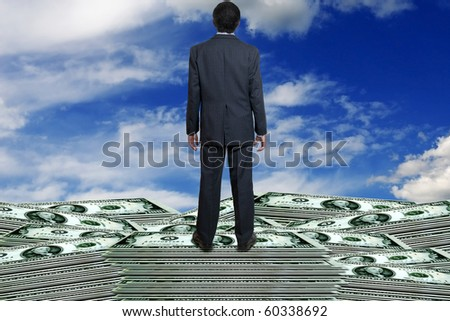 man in suit standing on banknotes - stock photo