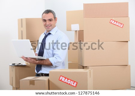 Man in suit surrounded by stacks of boxes