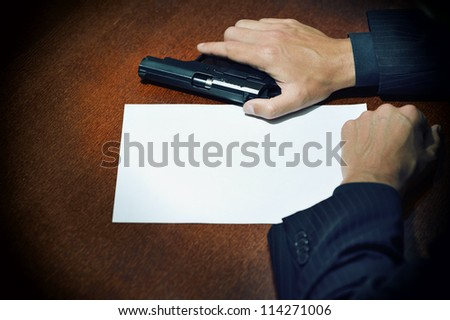 Man in suit takes gun, sitting at desk