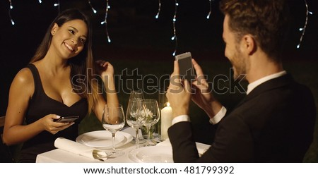 Man in suit takes photo of beautiful dinner date