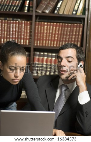 Man in suit talks on cell phone while seated. Woman leans over looking at laptop. Vertically framed photo. - stock photo