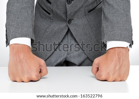 man in suit with his fists on the desk - stock photo