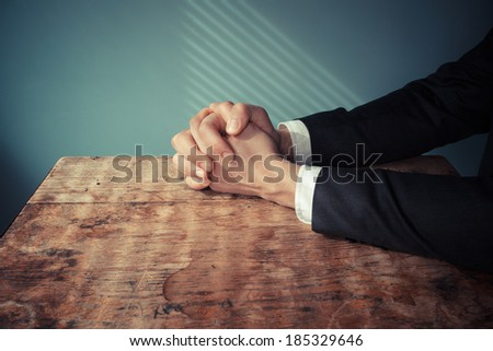 Man in suit with his hands folded in prayer at a desk with light streaming through blinds - stock photo